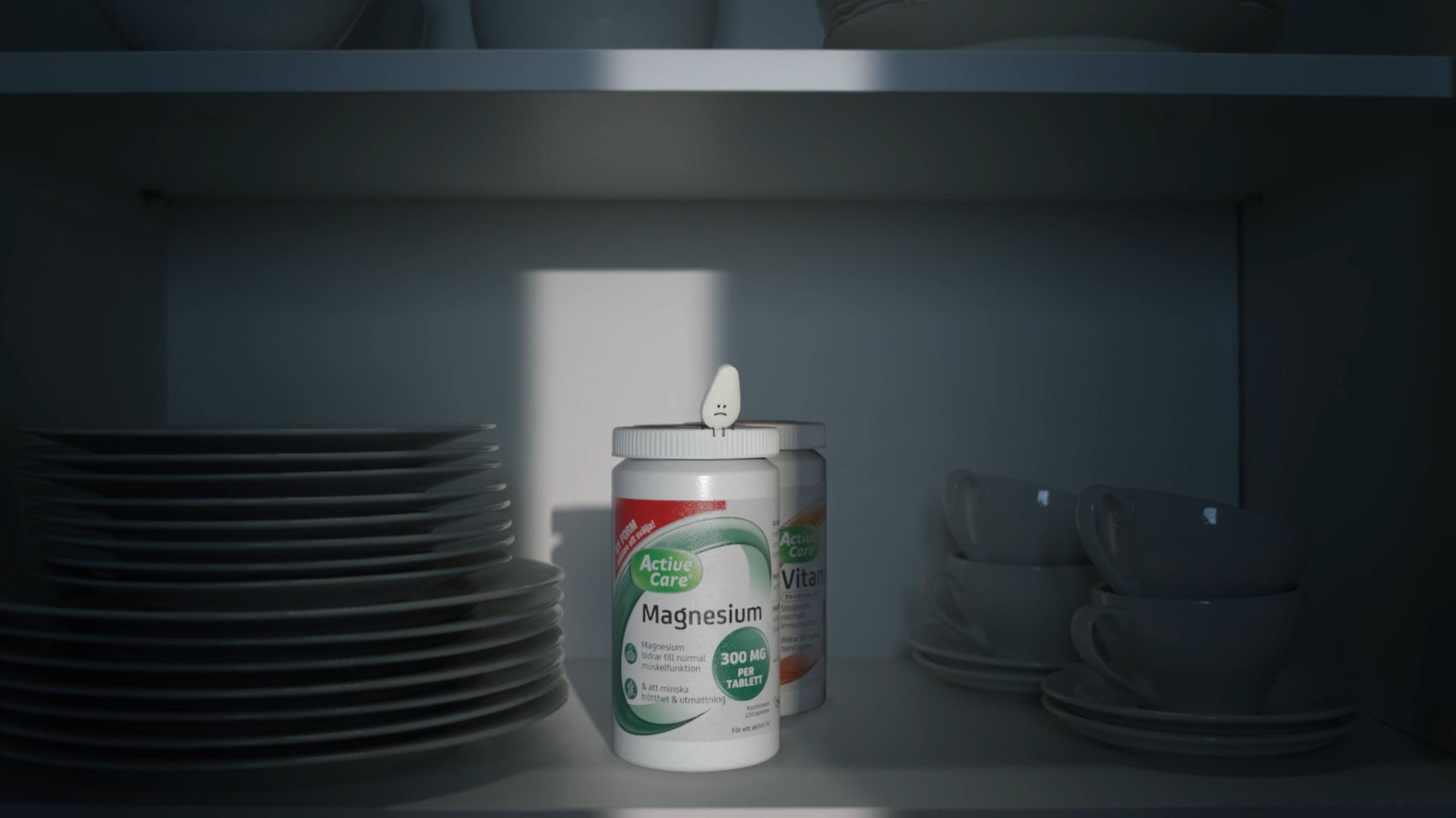 3d animasjon av orkla magnesium karakter sitter oppaa kapselboksen inne i kjoekkenskapet og ser trist ut